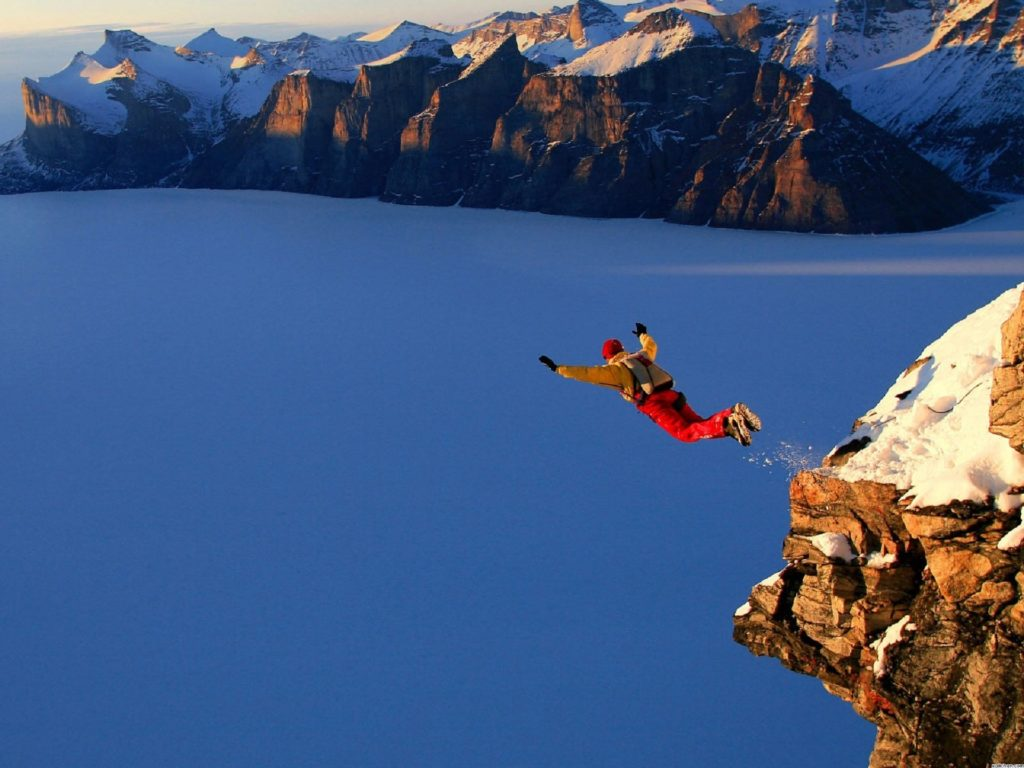 A man base jumping from a high ledge.