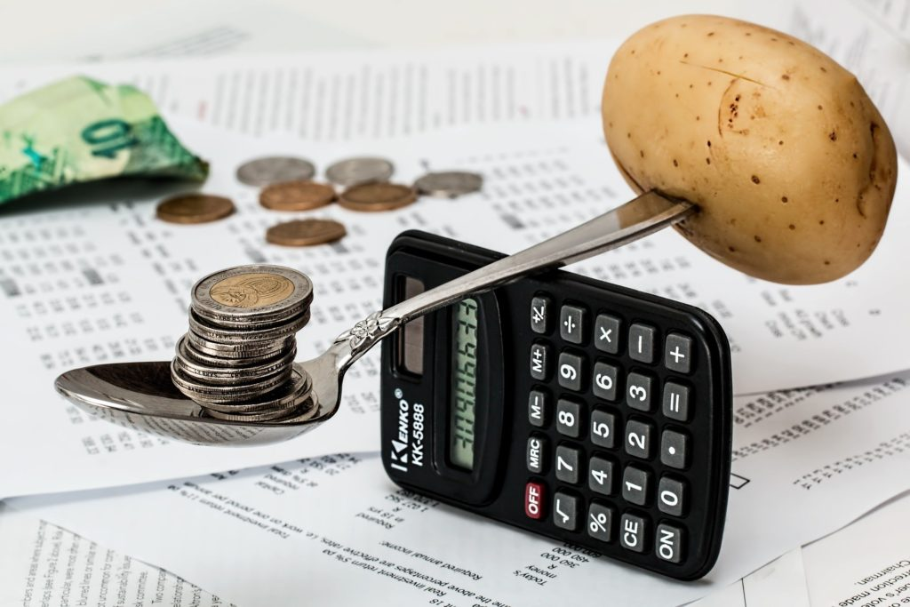 A spoon balancing on a calculator with coins on one end and a potato on the other.