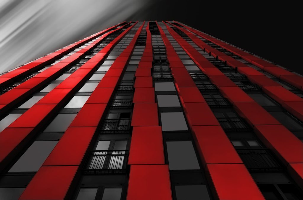 A black skyscraper with red accents extending upwards.