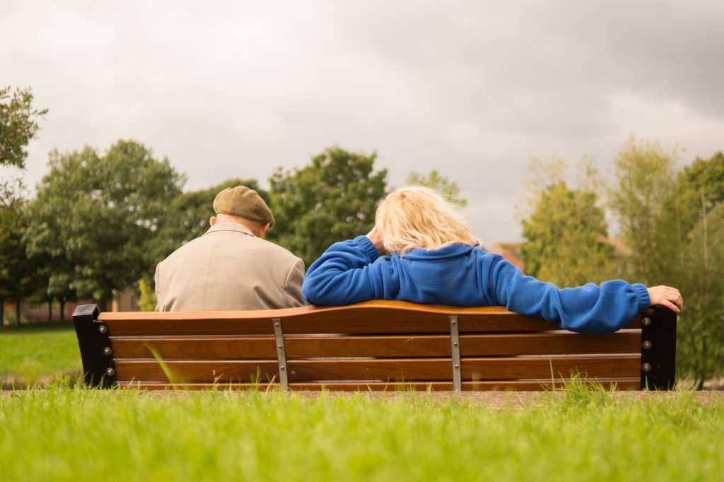 An old couple sitting on a bench facing away from the camera.