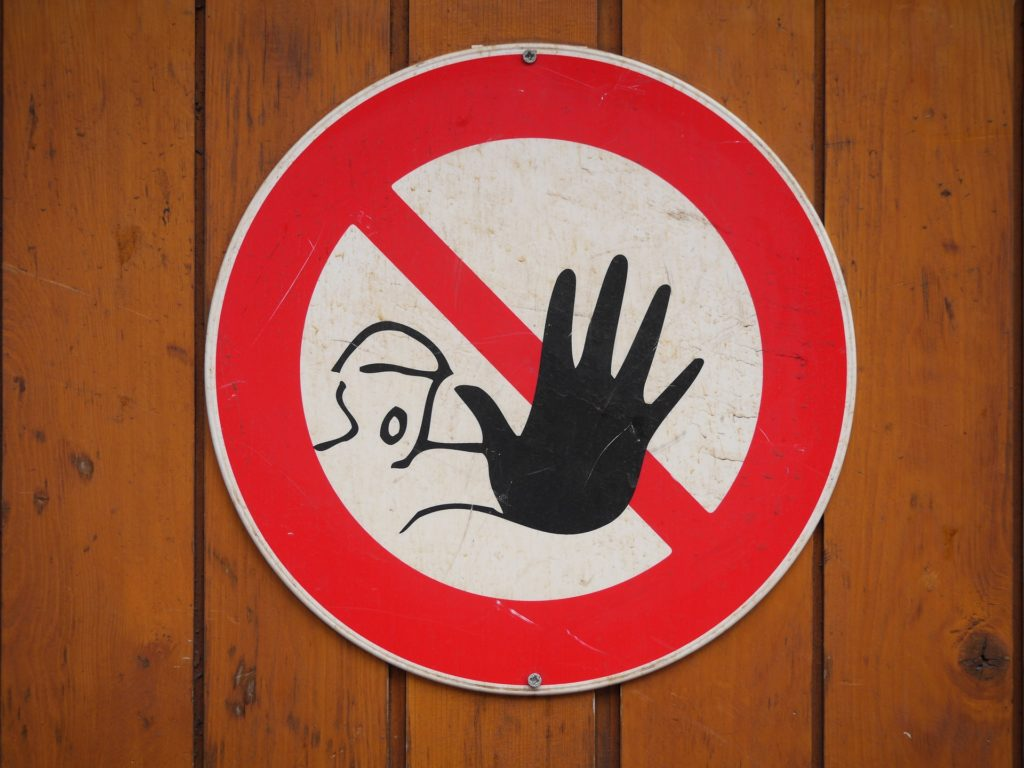 A warning sign depicting a man with his arm stretched out and mouth wide open.