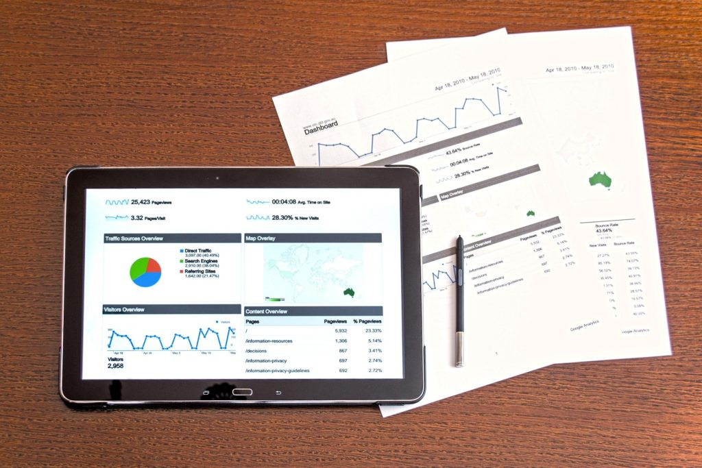 A tablet computer displaying financial graphs lays on a wooden table beside two physical financial statements and a pen.