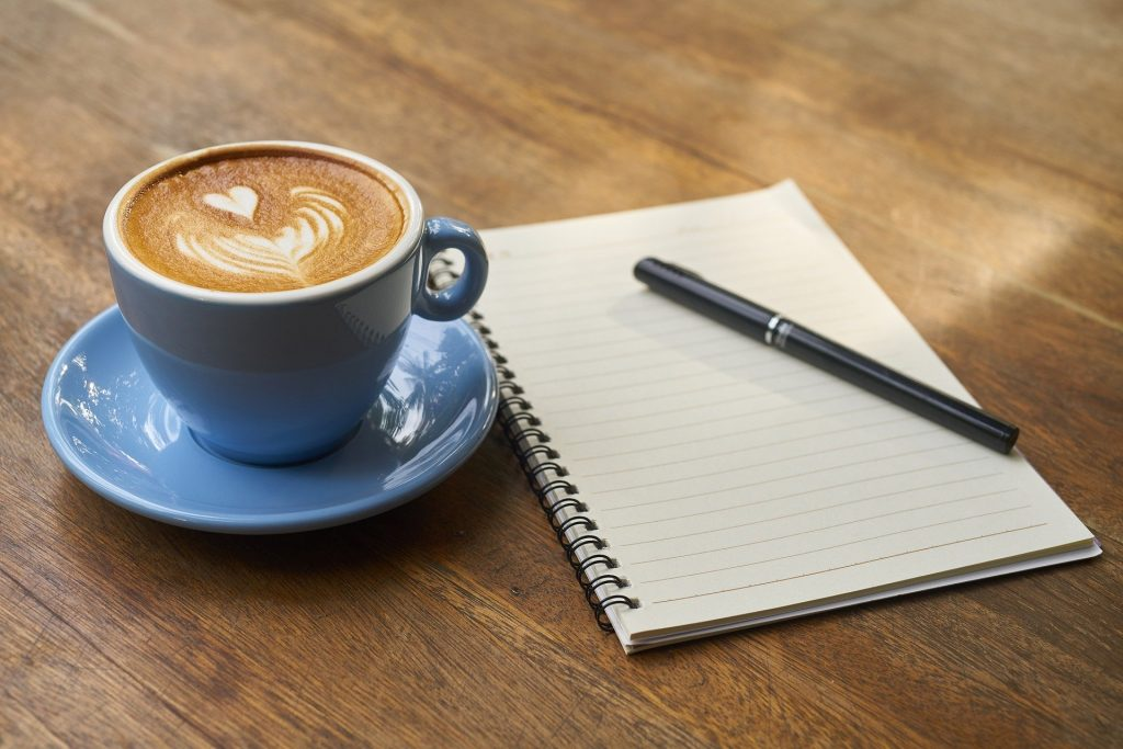 A fancy cup of coffee sitting on a wooden table beside a notebook and pen.