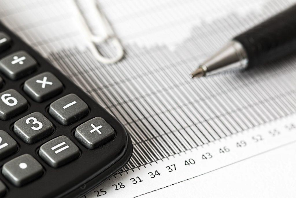 A calculator resting on top of a spreadsheet beside a pen.