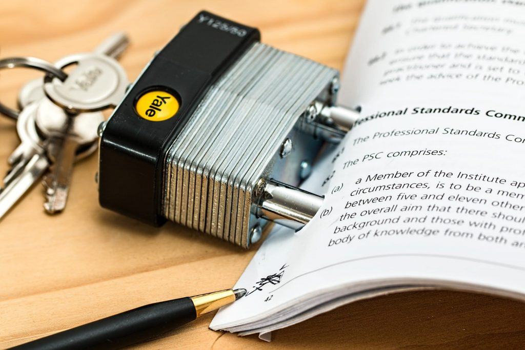 A lock holding several pieces of paper together to symbolize a contract.