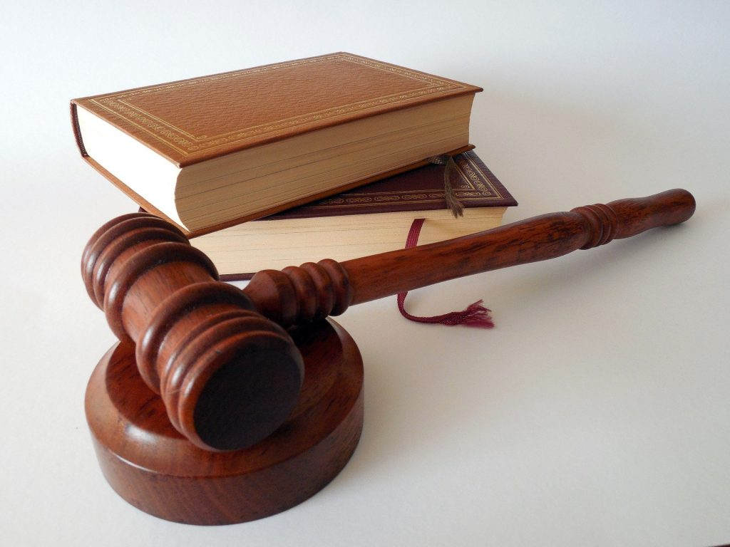 A judge's gavel resting beside a law textbook.