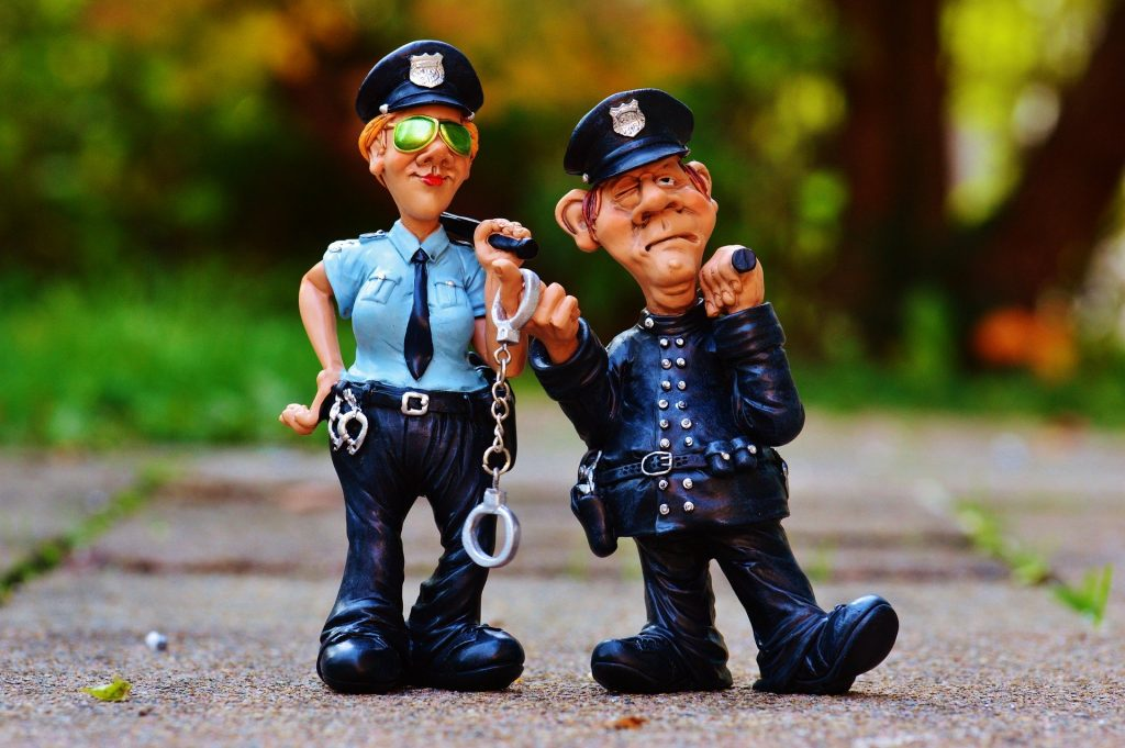 Police officer figurines standing on the pavement.