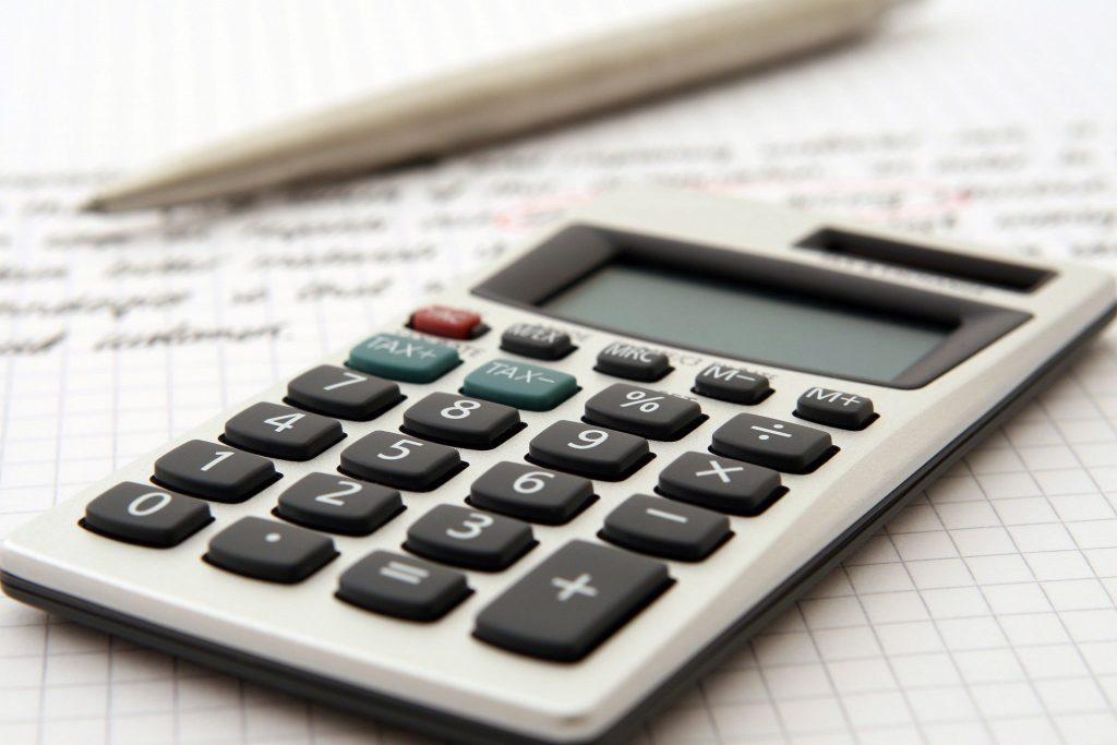 A calculator resting beside a pen.