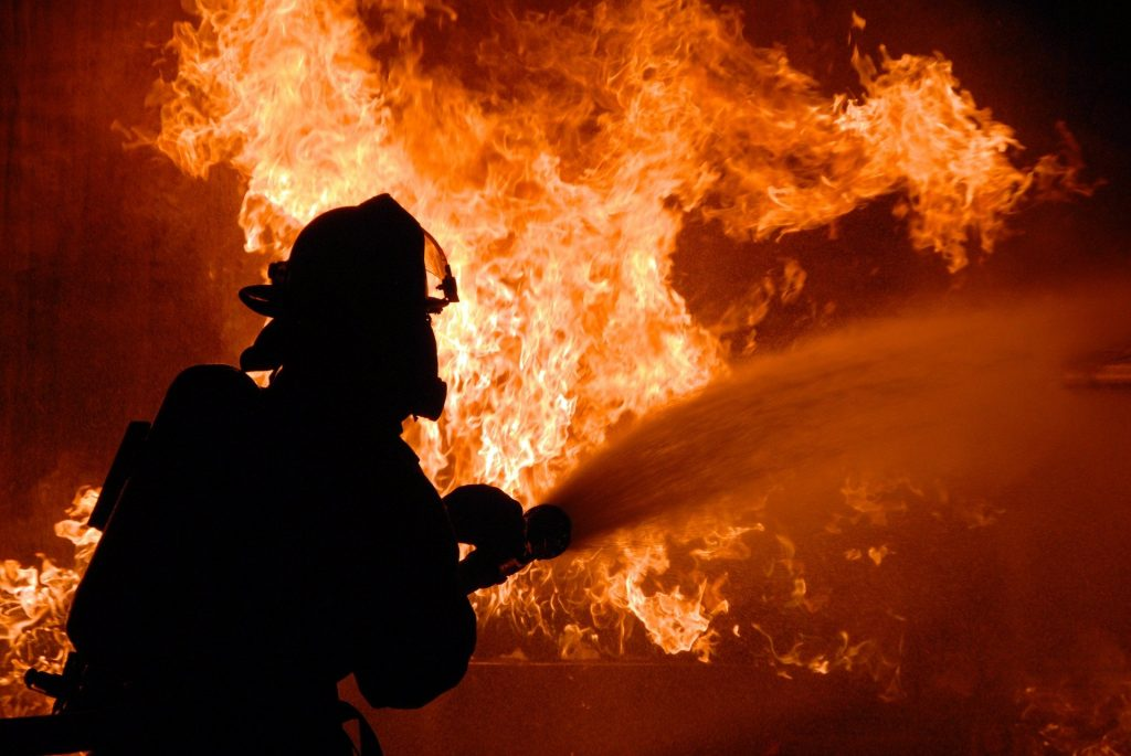 A firefighter aiming a hose at a blaze.