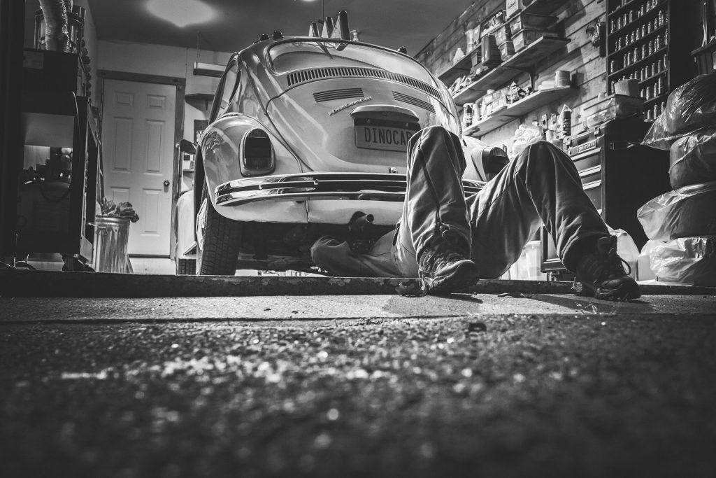 A mechanic underneath a Volkswagen Beetle.
