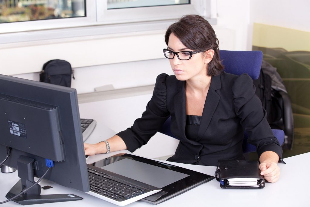 A young woman with brown hair and black glasses sits behind a computer at her office desk.