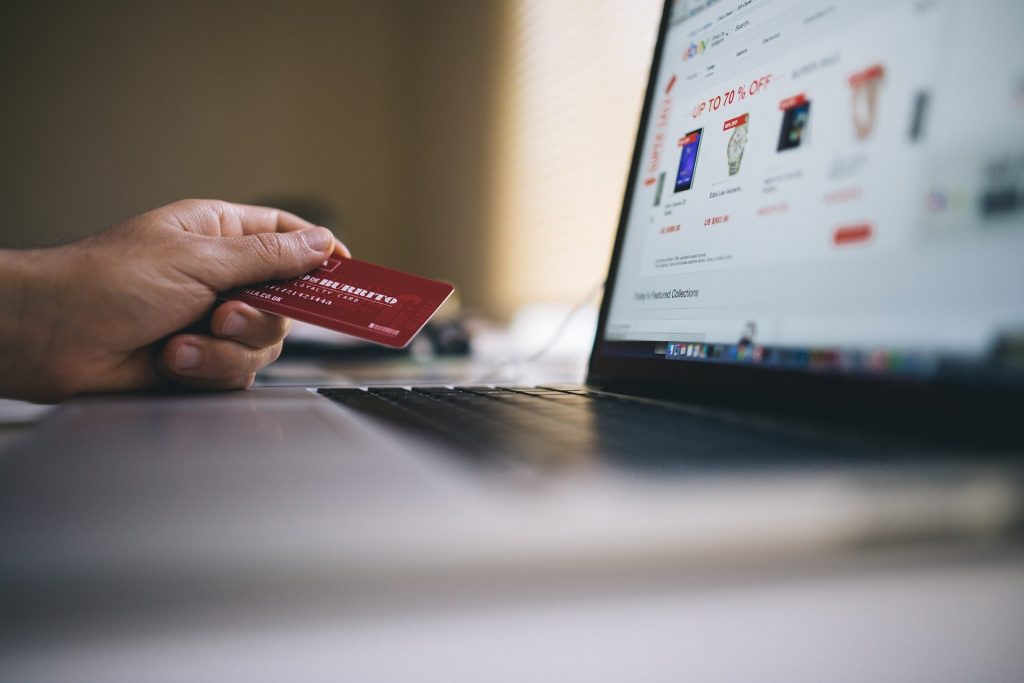 A man holding a credit card while online shopping.