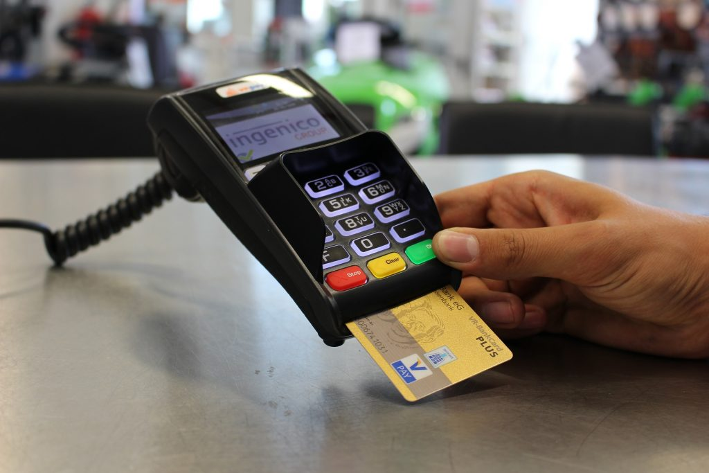 A golden credit card inserted into a payment machine.
