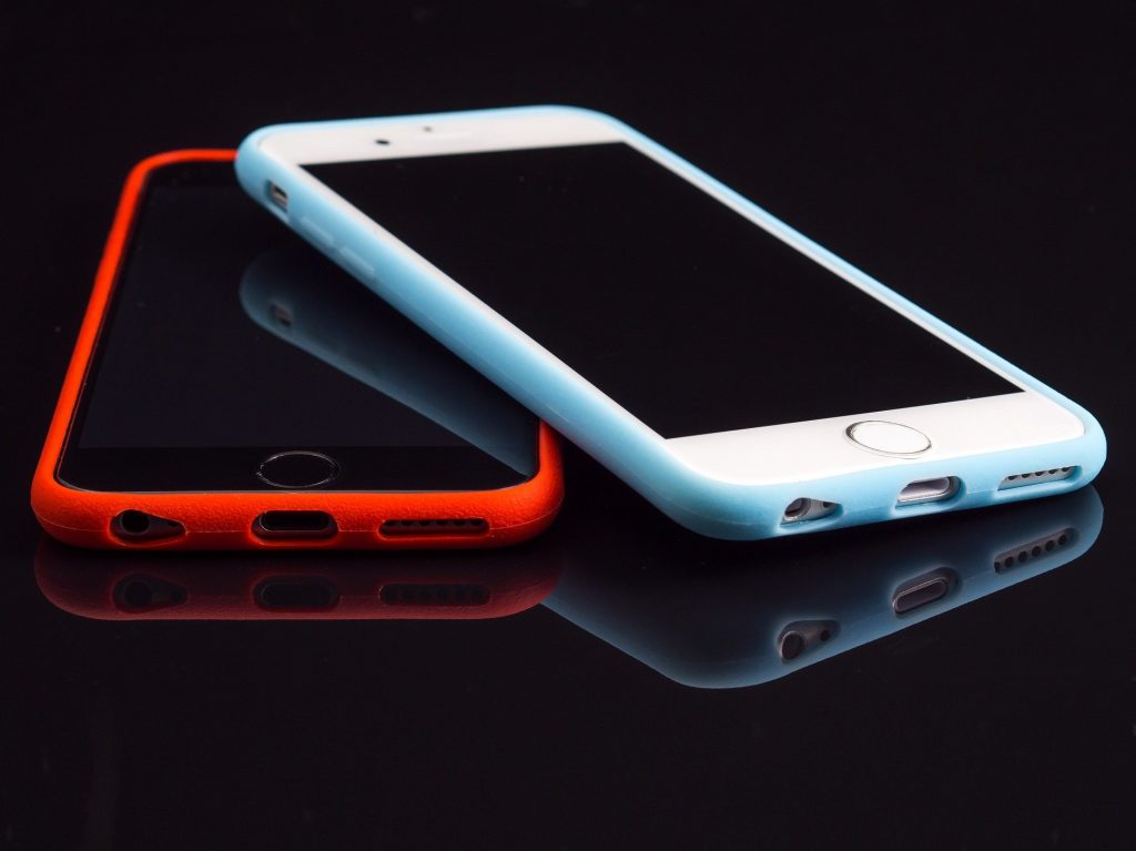 Two iphones sitting beside each other.