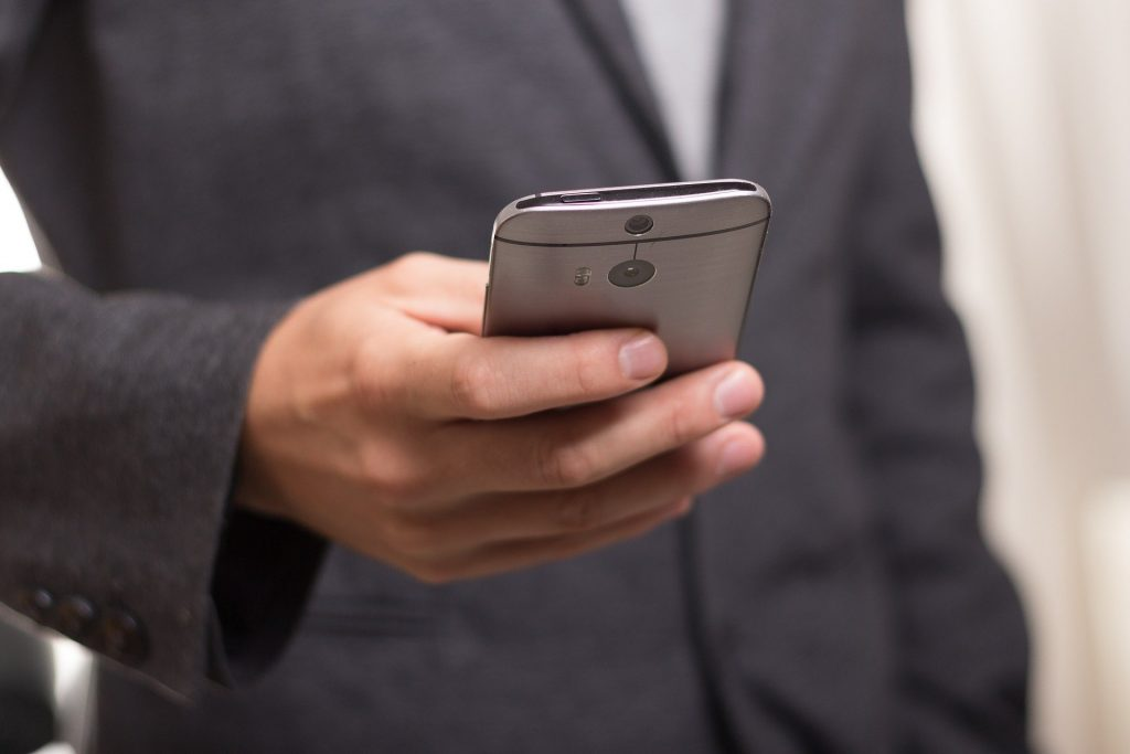 A man in a suit holding and using a smartphone.