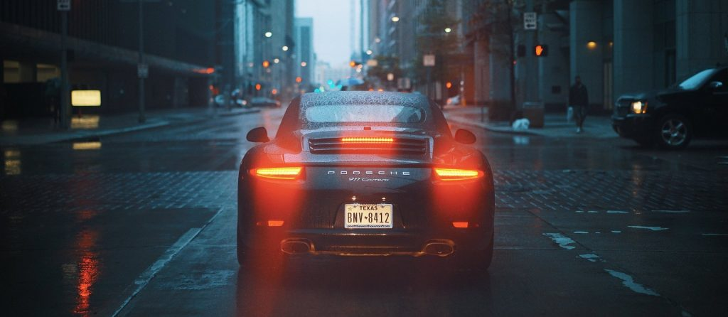 The rear end of a Porsche on a rainy city street.