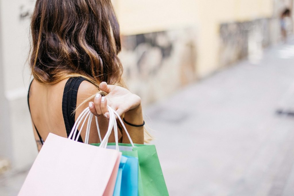 A woman with brown hair holding shopping bags behind her.