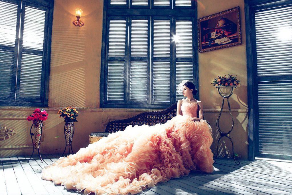 A woman in a very long, fancy pink dress.