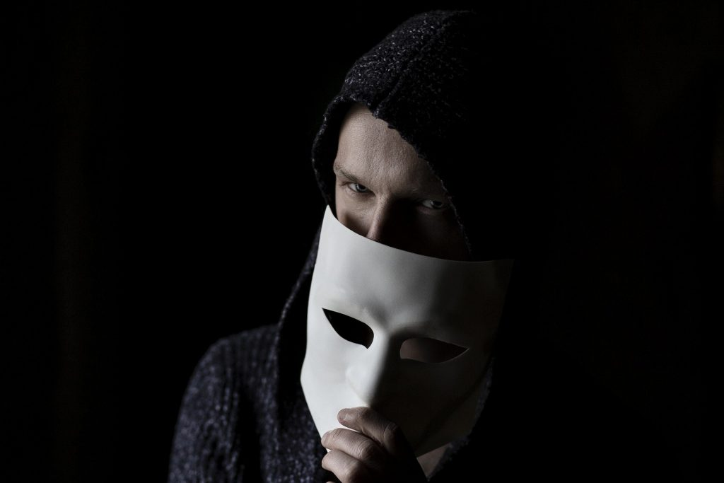 A man holding a mask in front of his face.