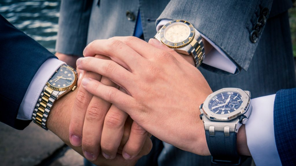 Three hands in a stack with nice watches on their wrists